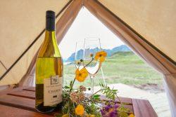 Glamping-Zelt mit Weinflasche und Blumen