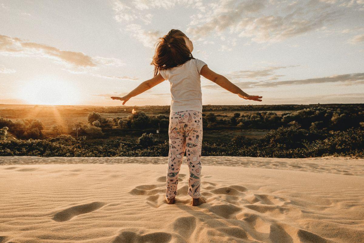 Kind vor Landschaft streckt Arme aus