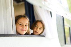Kinder schauen aus dem Wohnmobil-Fenster