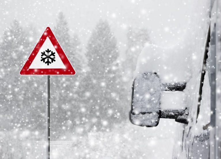Schnee-Warnschild auf verschneiter Straße