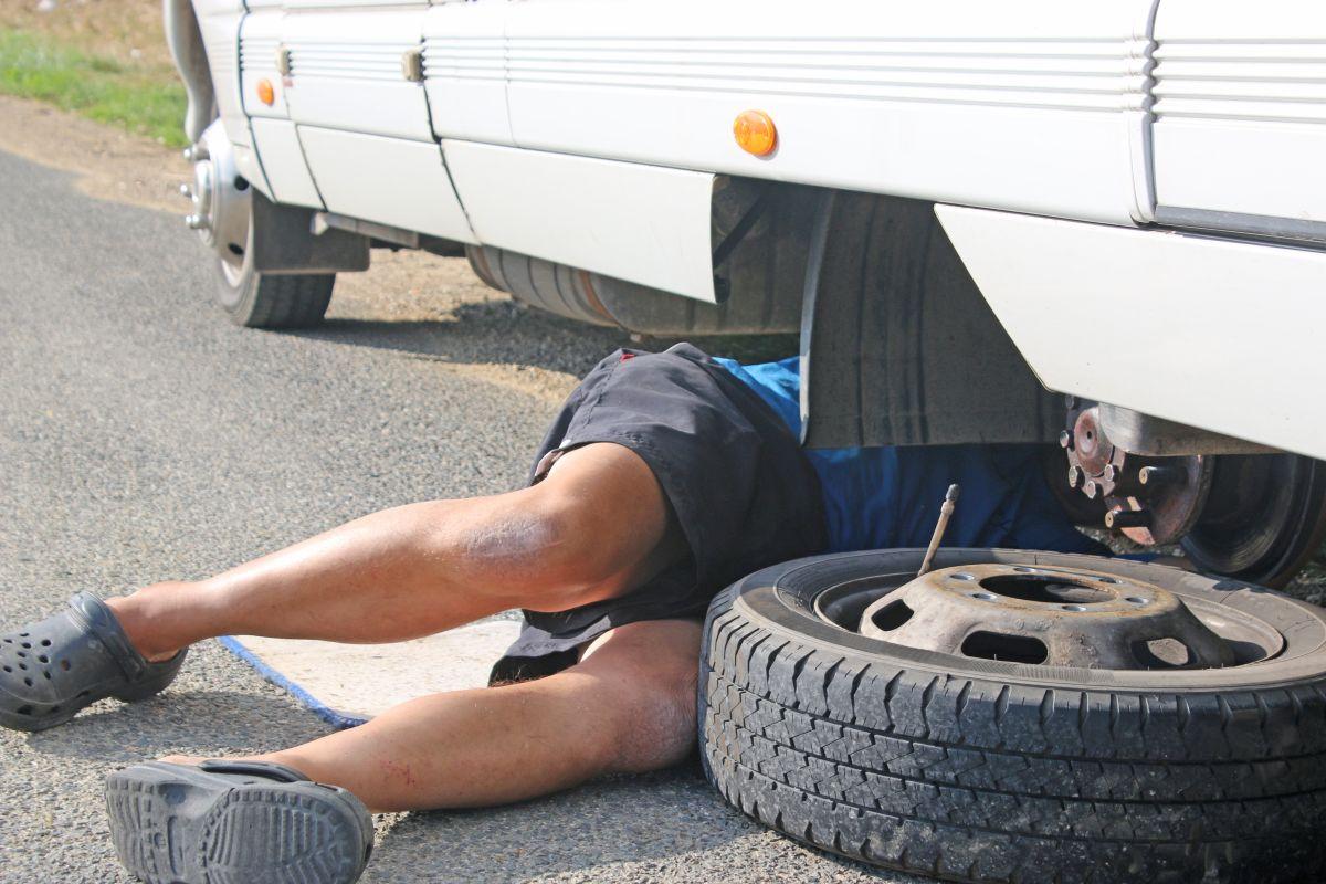 Mann wechselt Reifen am Wohnmobil